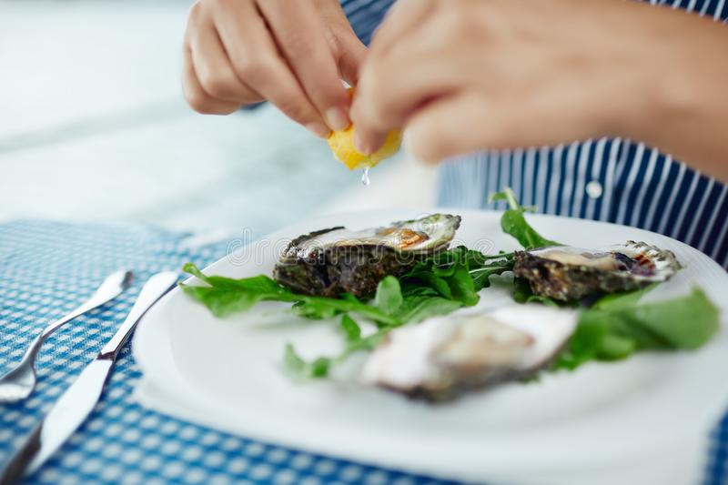 Women`s hands squeezing lemon juice on raw oyster, close up stock photography