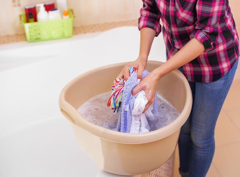Women`s hands wash clothes in the basin. Women`s hands wash clothes in the container. Close-up royalty free stock images