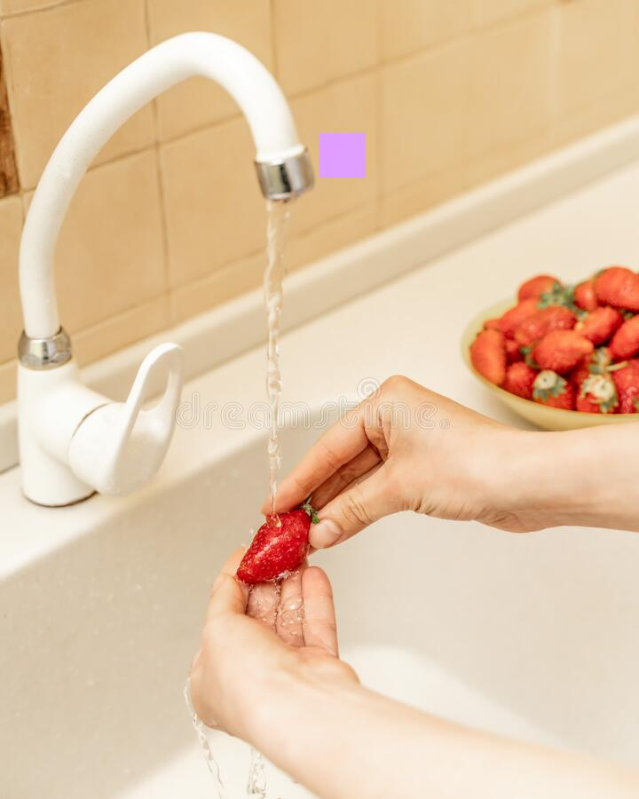 Women`s hands wash strawberries and blueberries under a stream of water in the kitchen sink. Selective focus. Wash fruit before. Women`s hands wash strawberries royalty free stock images