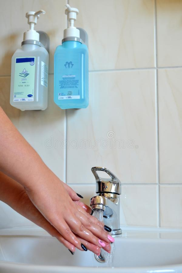 Women`s hands that are washed under water from the tap, hanging next to antiseptic hand washing stock images