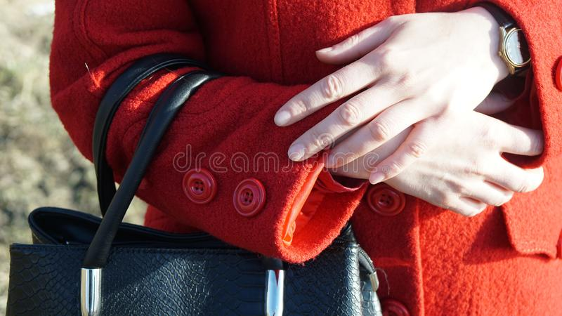 Women`s hands with a watch in a red coat. Fingers fashion beauty blonde hair black bag royalty free stock photos