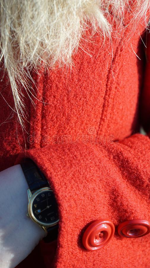 Women`s hands with a watch in a red coat red buttons. Women`s hands with a watch in a red coat fingers fashion beauty blonde hair red buttons stock photography