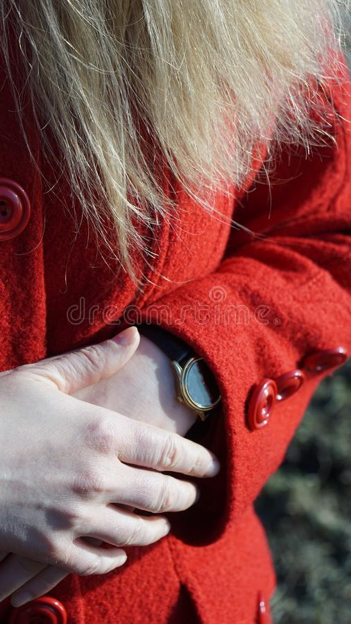 Women`s hands with a watch in a red coat. Fingers fashion beauty blonde hair stock image