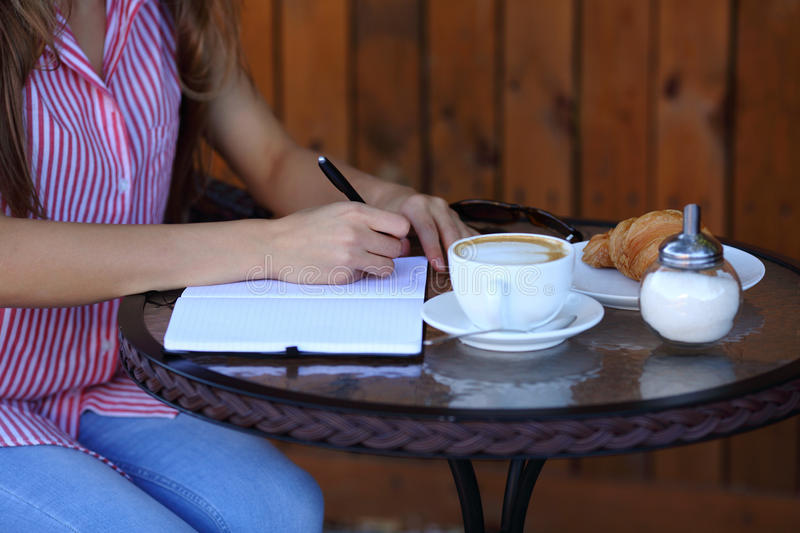 Women`s hands writting in diary with coffee royalty free stock photo