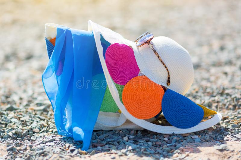 Women`s hat bag and glasses on the beach. Beautiful bright female things for leisure hat bag sunglasses lie on a pebble beach royalty free stock photos
