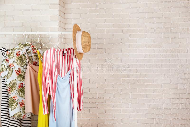 Women`s hip clothing store interior concept. Row of different colorful female clothes hanging on rack in hipster fashion show roo royalty free stock image
