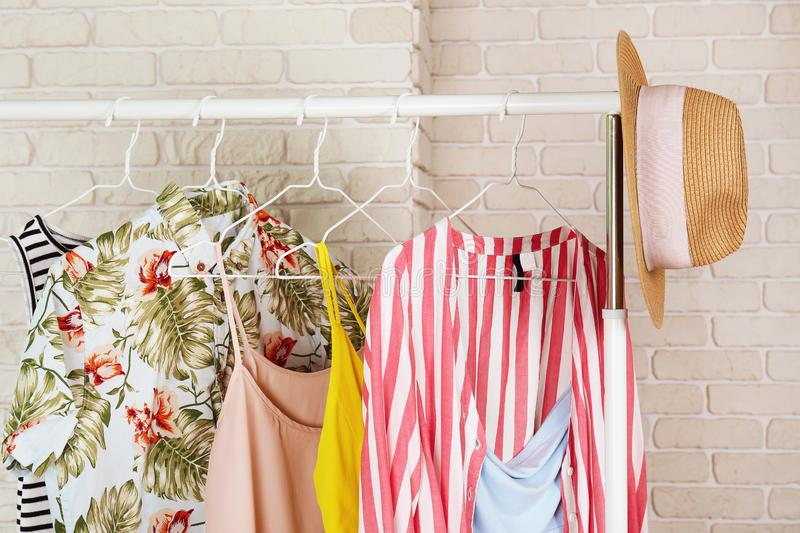 Women`s hip clothing store interior concept. Row of different colorful female clothes hanging on rack in hipster fashion show roo royalty free stock photos