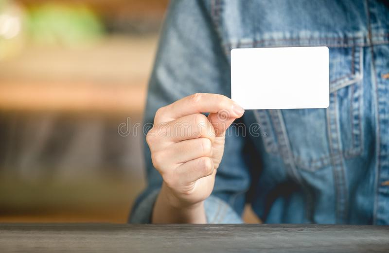 A Women`s Jean jecket is hand holding white business card for contact works. Blank paper card mock up stock image