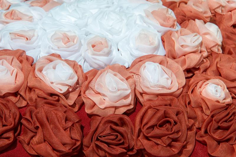 Women's jewelry made of silk fabric. White and red roses. The pl stock photos
