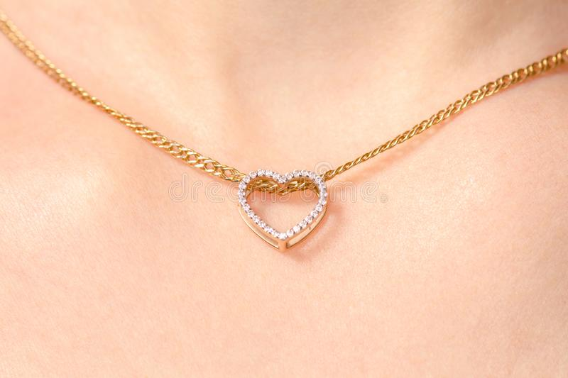 Women`s jewelry on the neck gold chain pendant heart royalty free stock images