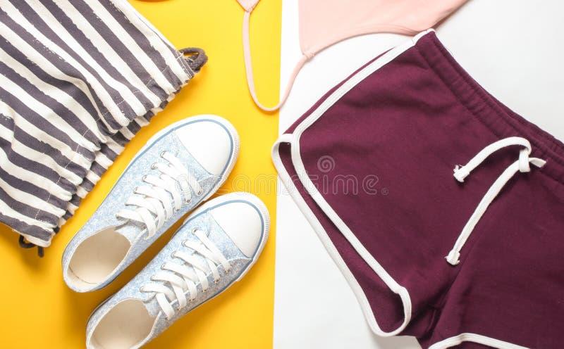 Women& x27; s-kläder och tillbehör för kondition på en kulör pastellfärgad bakgrund Gymnastiksko sportkortslutningar, påse, T-trö fotografering för bildbyråer