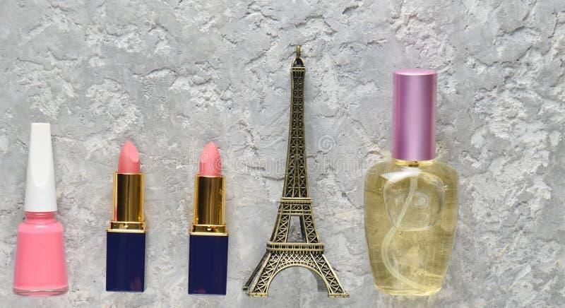 Women& x27; s kosmetyki od Paryż Dwa różowej pomadki, pachnidło butelka, gwoździa połysk, posążek wieża eifla fotografia royalty free
