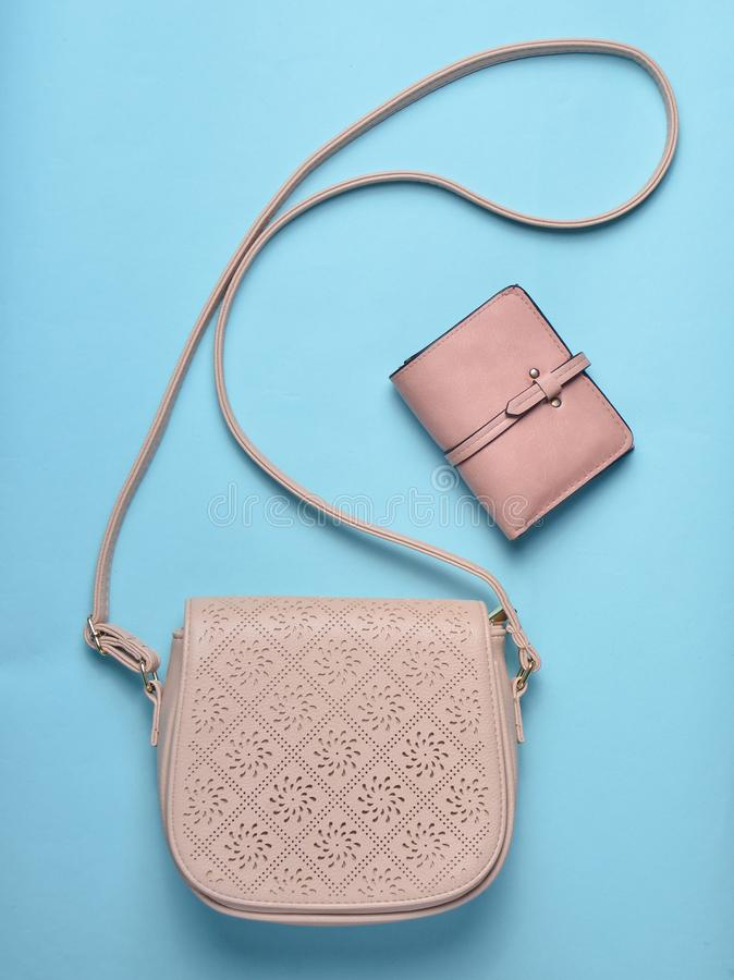 Women's leather bag and purse on a blue pastel background, women's accessories, top view, minimalism. Women's leather bag and purse on a blue royalty free stock photos
