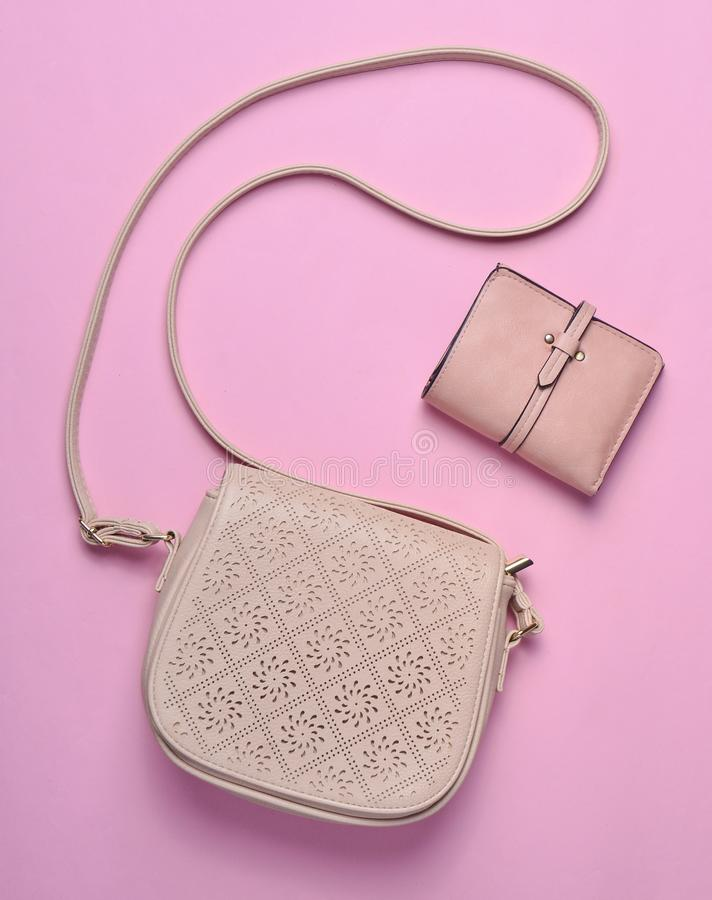 Women's leather bag and purse on a pink pastel background, women's accessories, top view, minimalism. Women's leather bag and purse on a pink royalty free stock photography