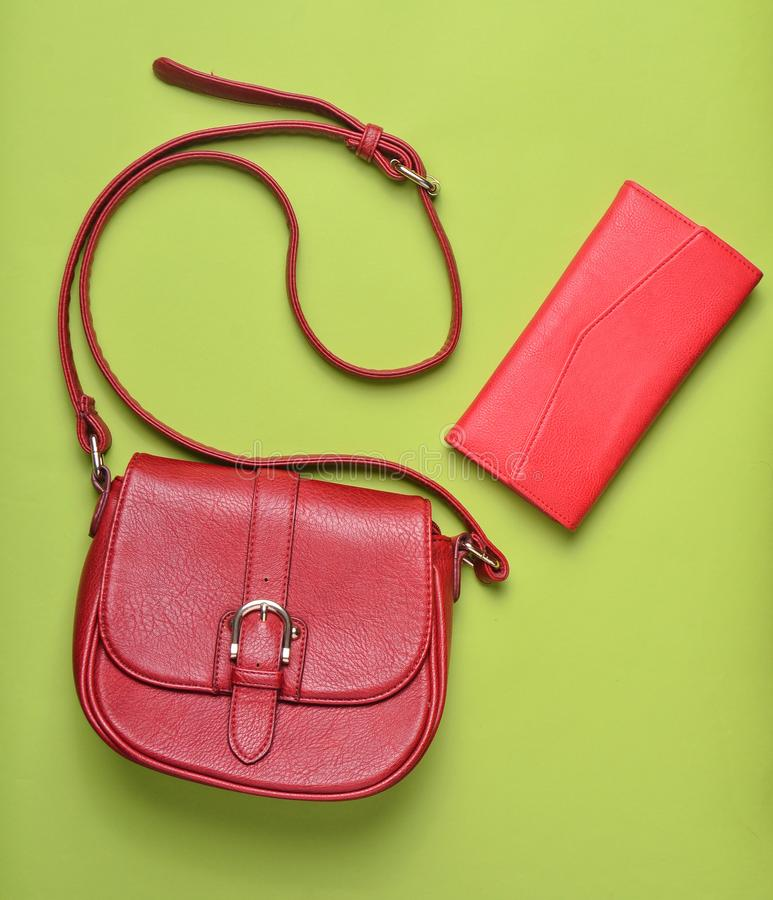 Women's leather red bag and purse on a green pastel background, women's accessories, top view, minimalism. Women's leather red bag and purse on a royalty free stock photography