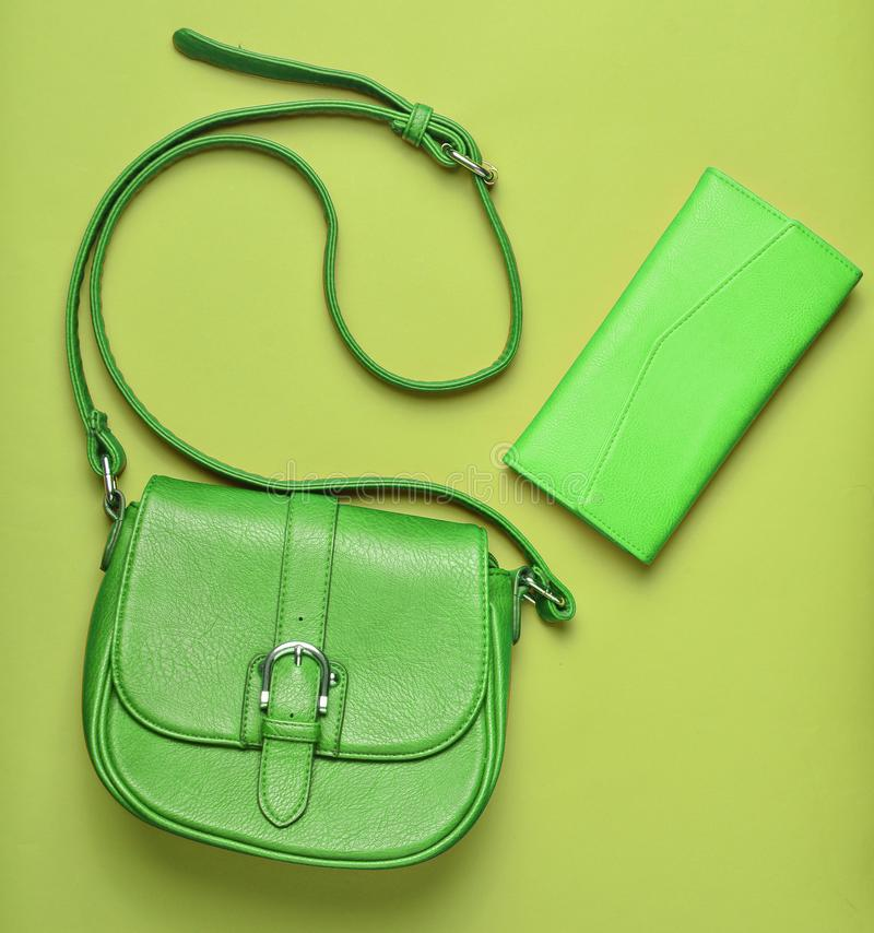 Women's leather red bag and purse on a green pastel background. Women's accessories, top view, minimalism royalty free stock image