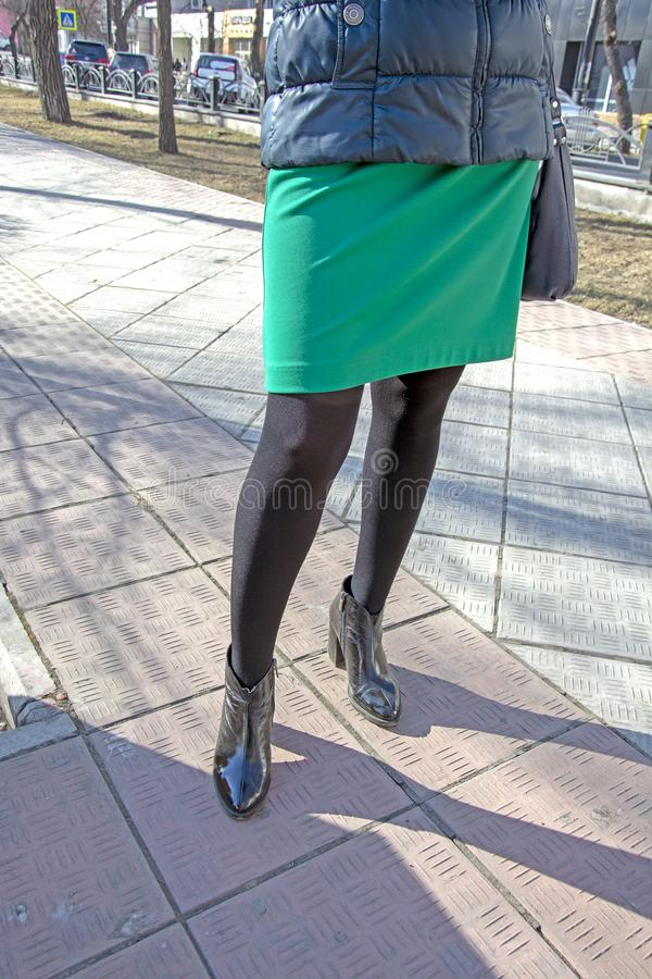 Women`s legs in black nylon pantyhose, in shoes with heels. On the street. Fetish. stock photo