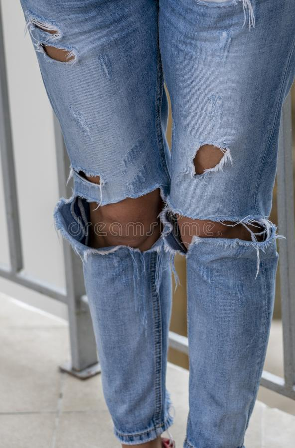 Women`s legs dressed in jeans with holes stock photo
