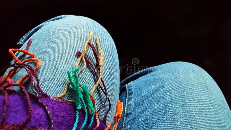 Women`s Legs - knees of sitting woman in denium jeans draped with multipcolor fringe from scarf. Legs - knees of sitting woman in denium jeans draped with royalty free stock photo