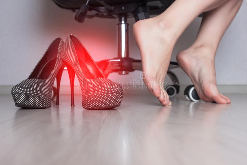 Women`s legs in the office hanging from the office chair that itch due to a fungal infection contagious shoes copy space medicinal. Women`s legs in the office royalty free stock images