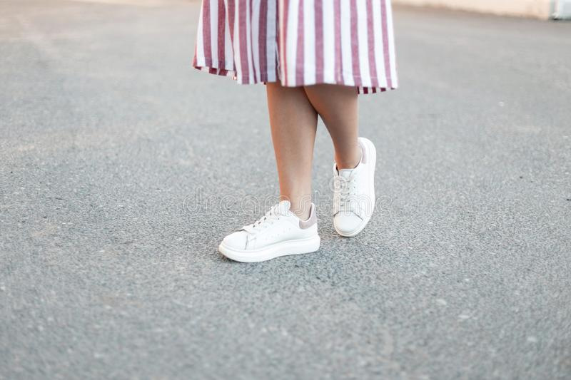 Women`s legs in a stylish pink long dress in fashionable white leather sneakers stand on the pavement. stock image