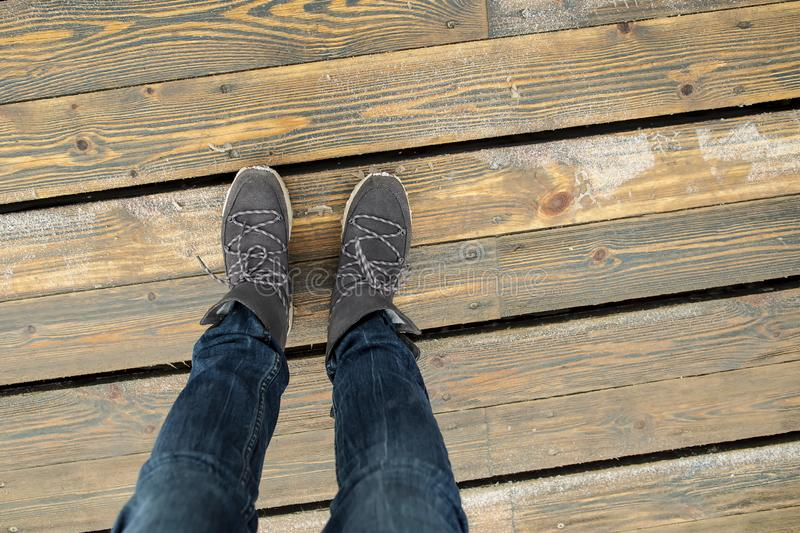 Women`s legs in stylish suede boots stand on a bridge of wooden planks on a cold, winter day. Top view stock image