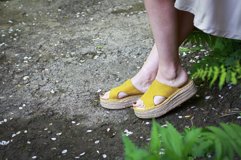 Women`s legs in stylish summer sandals with straw soles, concept of comfortable shoes, side view royalty free stock images