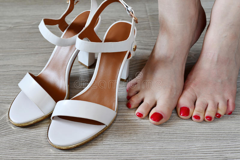Women's legs and white sandals royalty free stock image