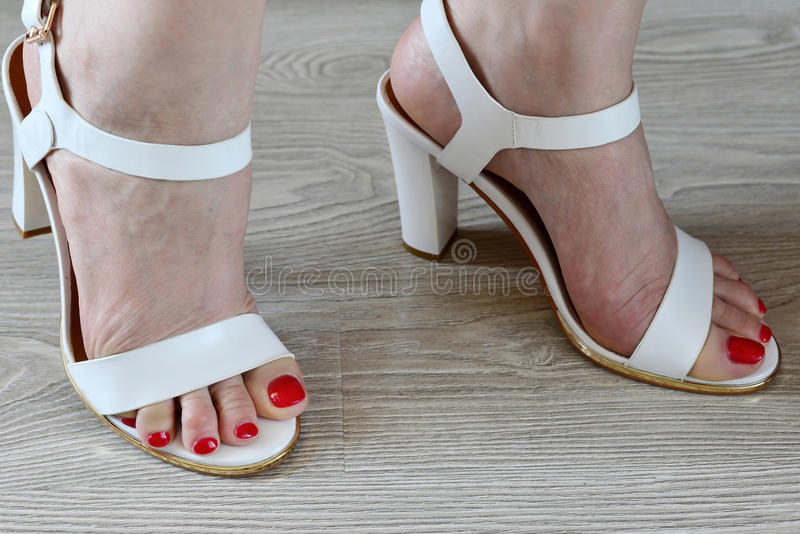 Women's legs and white sandals royalty free stock photos