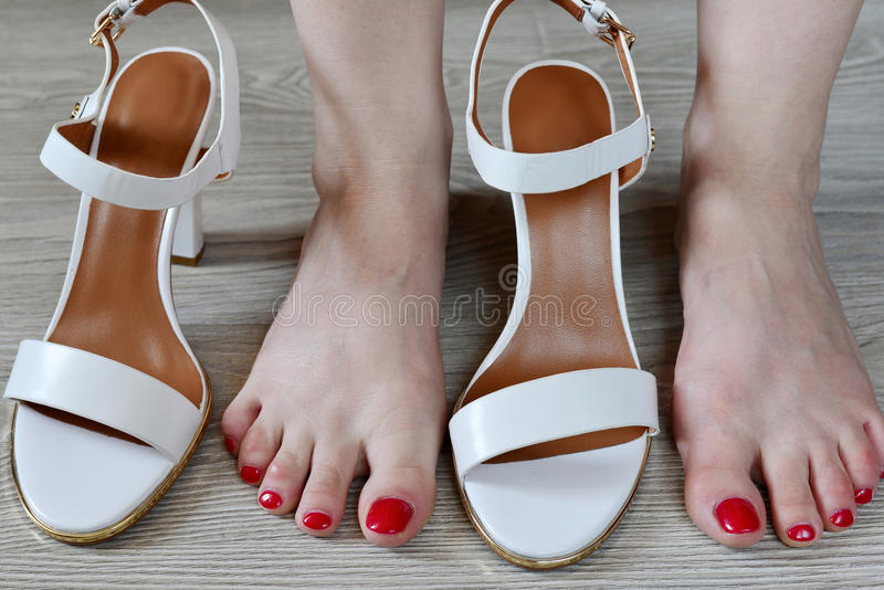 Women's legs and white sandals stock images