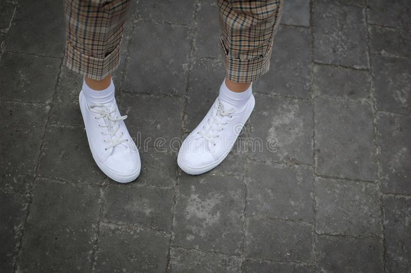 Women`s legs with white sneakers and bringht pants on the road during spring or summer time outdoors stock images