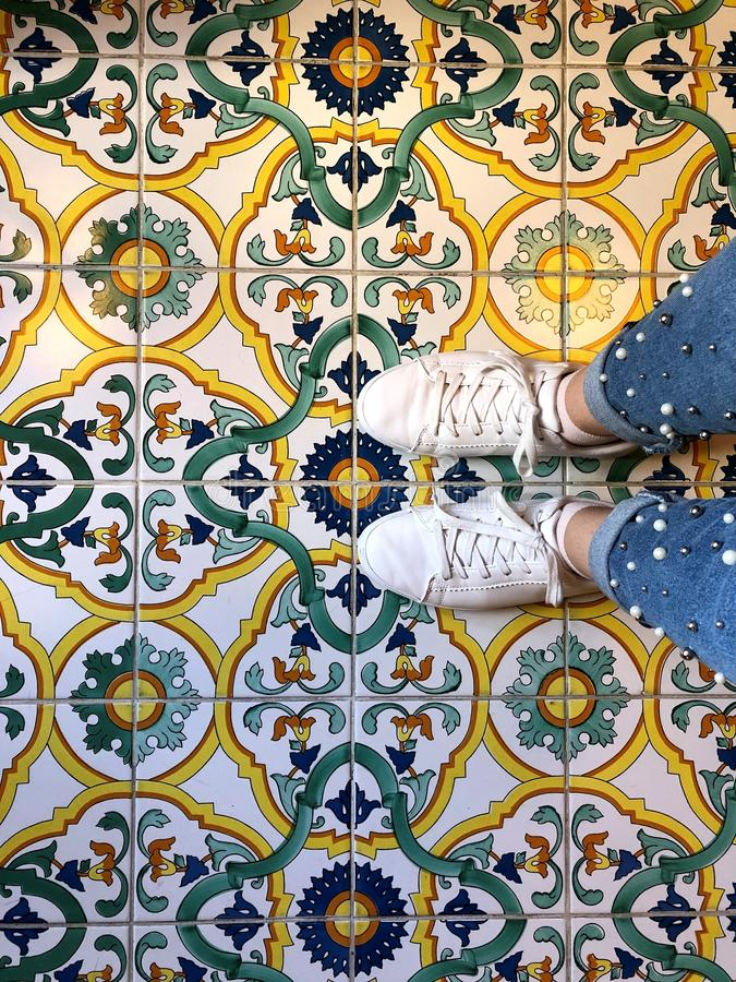 Women`s legs in white sneakers on the floor. With Oriental ornaments and patterns royalty free stock image
