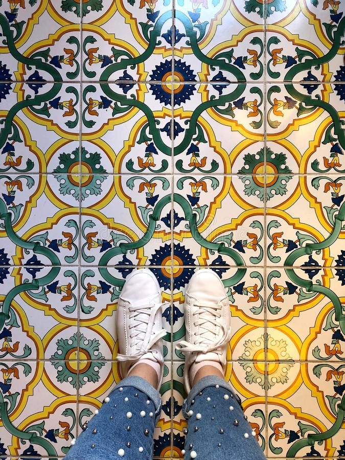 Women`s legs in white sneakers on the floor. With Oriental ornaments and patterns royalty free stock photo