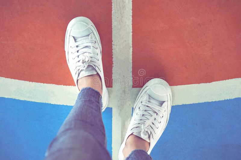 Women`s legs in white sneakers are standing on the choice. Women`s legs in white sneakers are standing on the choice of whether to go left or right royalty free stock image