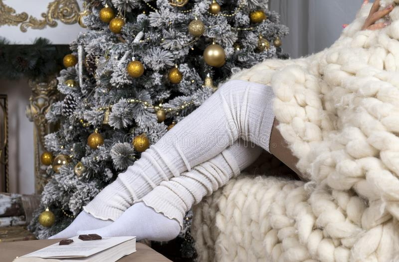 Women`s legs in white socks, white knitted blanket, a Christmas. Tree decorated with pine cones and gold balls, a book ,a piece of chocolate, the eve of the royalty free stock photography