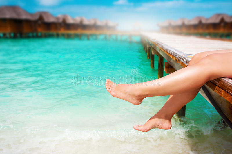 Women`s legs at wooden pier of tropical island. Resort stock photos