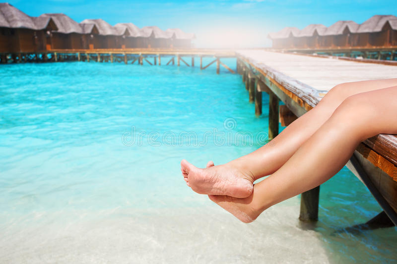 Women`s legs at wooden pier of tropical island. Resort royalty free stock photo