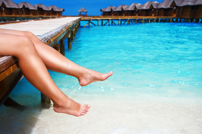 Women`s legs at wooden pier of tropical island. Resort royalty free stock images
