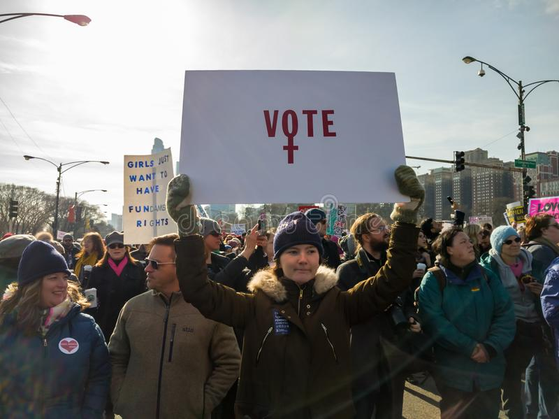 2018 Women`s March in Chicago. A young woman encourages voting. GRANT PARK, CHICAGO, USA-January 20, 2018. Women`s March. A young woman holds a sign that reads stock photos