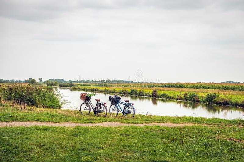 Women`s and men`s bicycle parked along the water of a stream stock images