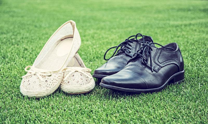 Women`s and men`s wedding shoes on grass. Women`s and men`s wedding shoes on the green grass. Symbol of love. Blue photo filter stock photography