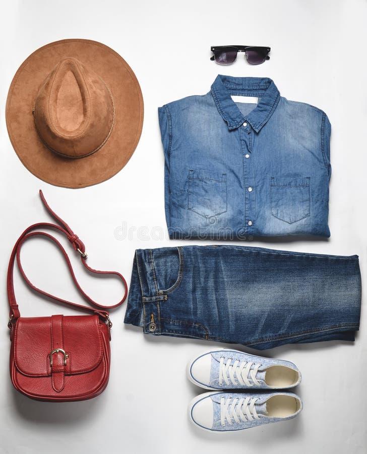 Women& x27; s mody akcesoria i odzież Cajgi, drelichowa koszula, sneakers, odczuwany kapelusz, rzemienna torba, okulary przeciwsł fotografia stock