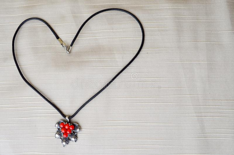 Women`s necklace with a silver pendant with red circles in the form of a heart made of black thread royalty free stock images