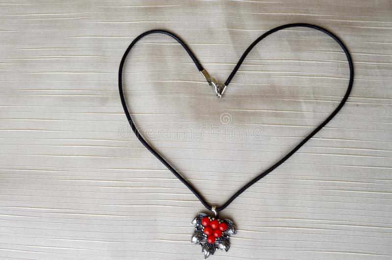 Women`s necklace with a silver pendant with red circles in the form of a heart made of black thread stock images