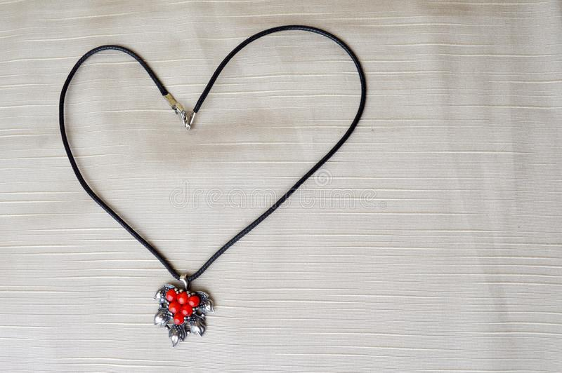 Women`s necklace with a silver pendant with red circles in the form of a heart to the day of St. Valentine made of black thread royalty free stock photos