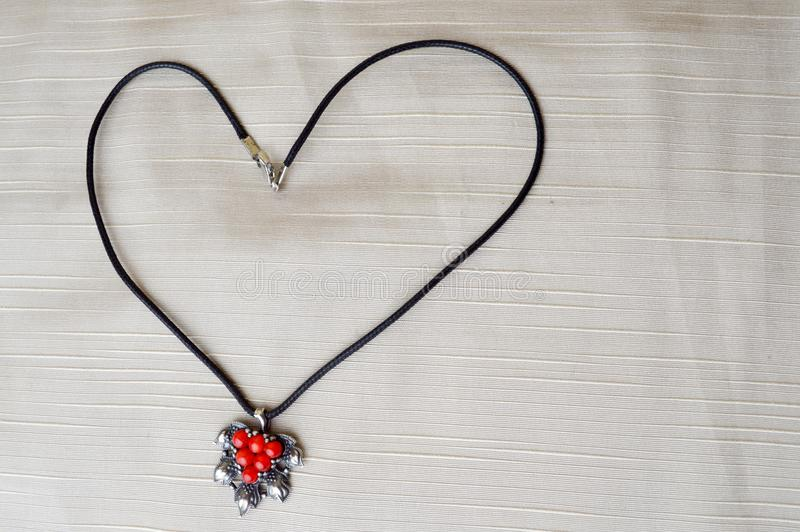 Women`s necklace with a silver pendant with red circles in the form of a heart to the day of St. Valentine made of black thread stock photography