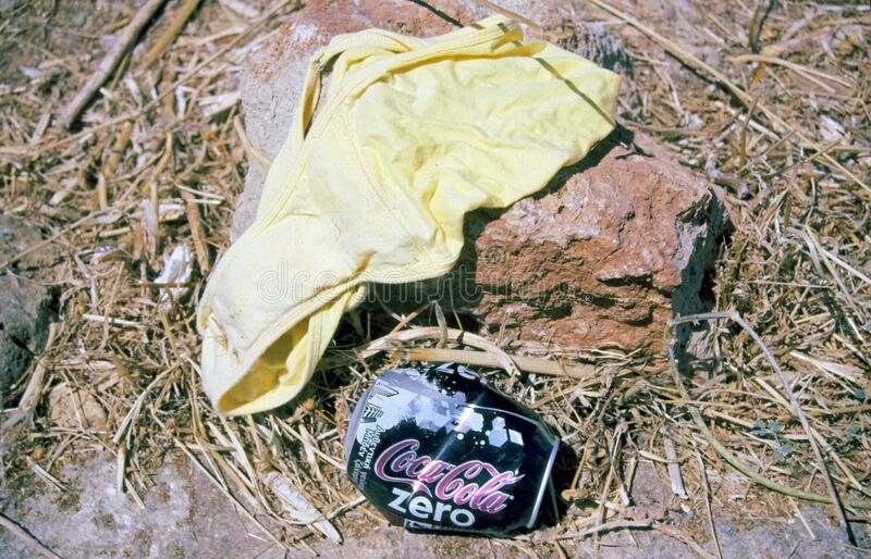 Women`s panties and empty coca cola lying on dry and yellow grass royalty free stock photography