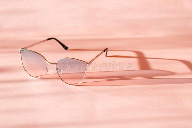 Metal frame sunglasses cast a shadow on the pink surface. Summer is coming concept. royalty free stock photo