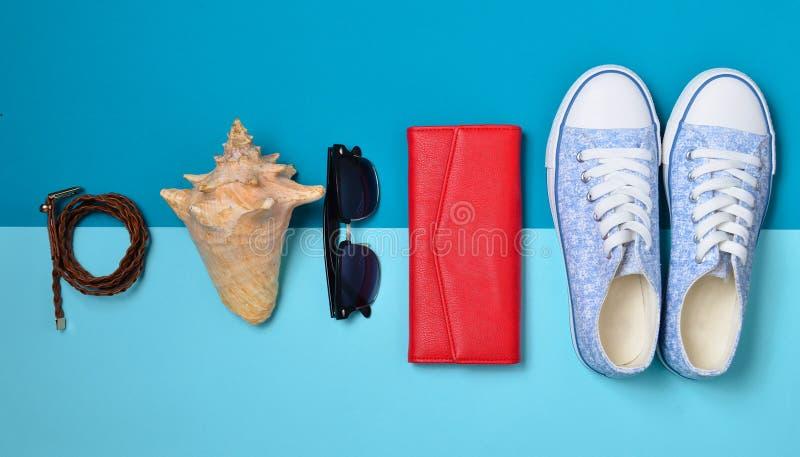 Women& x27; s-Schuhe und Reisezubehör auf einem blauen Pastellhintergrund Tasche, Geldbeutel, Turnschuhe, Oberteil, Gurt Flache L lizenzfreie stockfotos