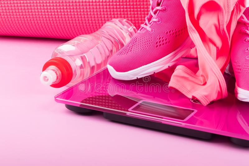 Women`s set of shoes, clothes and accessories in pink for fitness on a pink background royalty free stock images
